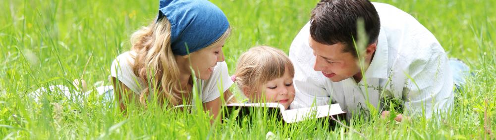 young family with daughter reads Bible